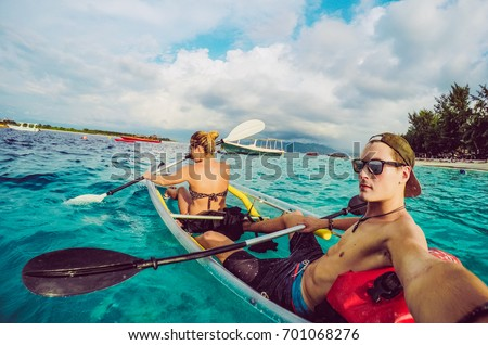 Couple of boyfriend and girlfriend riding small boat in Bali island, Indonesia. Selfie of best friends while using kayak and doing sport. Concept of active people enjoying holiday and sharing moments