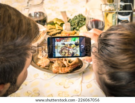 Couple of boyfriend and girlfriend taking a food selfie in dinner restaurant - Moda of catching the instant with modern smartphone at lunch meeting with typical italian food - Warm filter