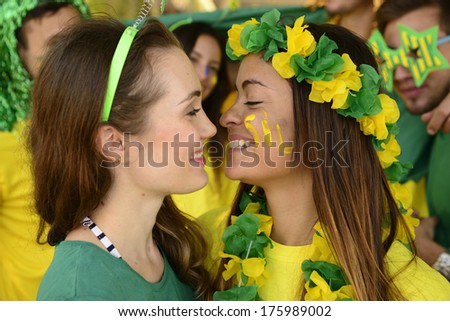 Couple of brazilian girlfriend sport soccer fans almost kissing each other celebrating.