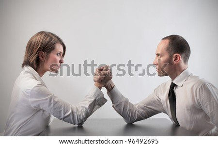 Couple of business people playing arm wrestling