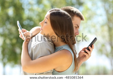Couple of cheaters hugging and texting everyone on their smart phones