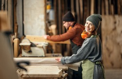 Couple of cheerful carpenters with wooden details in hands working together near workbench in professional workroom