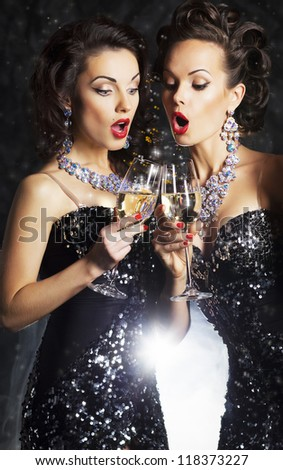 Couple of cheerful women toasting at party with wineglasses - celebration. Formal Party