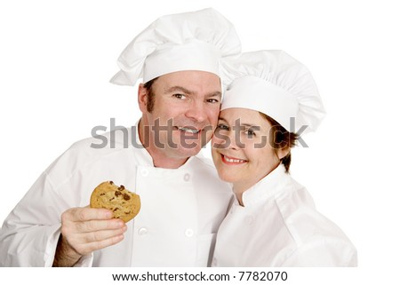 Couple of chefs smiling and enjoying a cookie.  Isolated on white.
