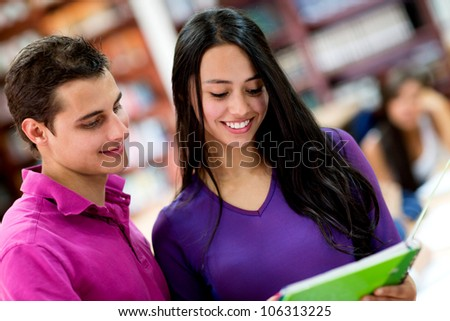 Couple of college students reading notes on a notebook