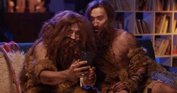 Couple of Comical Neanderthals Covered in Fur Using Mobile Phone Taking Selfie Learning Technology. Evolution of Mankind. Time Travel. Movie Concepr.