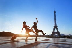 couple of crazy tourists on holidays in Paris, man and woman having fun near Eiffel Tower, travel with luggage, tourism