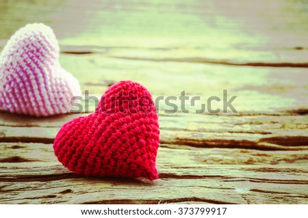 Couple of crochet heart in red and pink over wooden background. Photo is focused at the red heart. #373799917