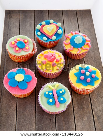 Couple of cupcakes with marzipan decoration on wooden background