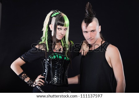 Couple of cyber punk girl with green blond hair and punk man with mohawk haircut. Expressive faces. Isolated on black background. Studio shot.