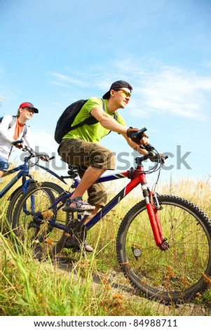 Couple of cyclists riding bicycles in countryside