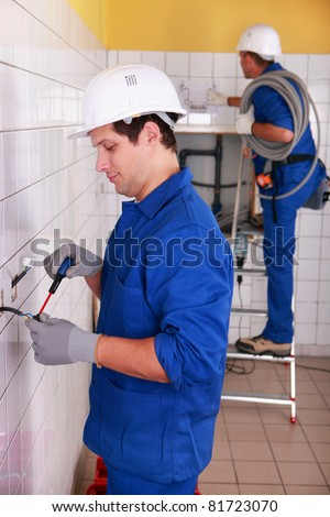 Couple of electricians wiring a building - stock photo