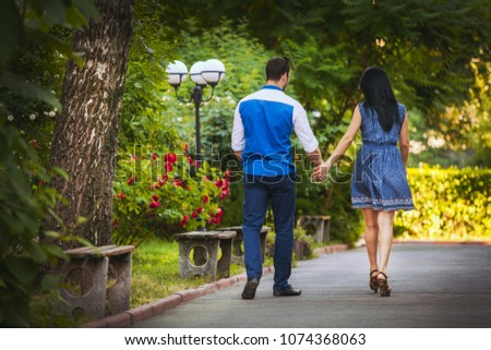 couple of enamored are walking in the park in the summer #1074368063