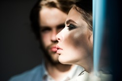 Couple of fashion models. Girl with makeup, eyeshadows, blush, foundation. Cosmetics, beauty, visage concept. Skin care, treatment, health. Woman face profile with blurred man on background.