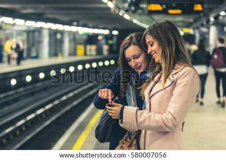 Couple of female friends looking at the smartphone while waiting for the train on the tube. Two young women checking on the phone before boarding. Tone added