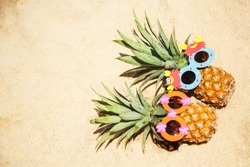 Couple of funny attractive pineapples in children's cheerful sunglasses lying on the white sand on the tropical beach. Tropical summer vacation concept. Happy sunny day on the beach of tropical island