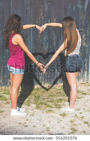 Couple of girls making an heart shaped shadow with arms. They are two girls wearing summer clothes outdoor. They are joining their arms drawing an heart on a wood background.