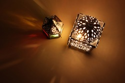 Couple of glowing Moroccan ornamental lanterns on table. Decorative golden shadows. Greeting card, invitation for Muslim holy month Ramadan Kareem. Festive background. Flat lay, top view.