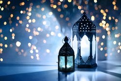 Couple of glowing Moroccan ornamental lanterns on the table. Greeting card, invitation for Muslim holy month Ramadan Kareem. Festive blue night background with glittering golden bokeh lights.