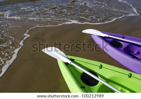 Couple of green and purple kayaks on the beach.