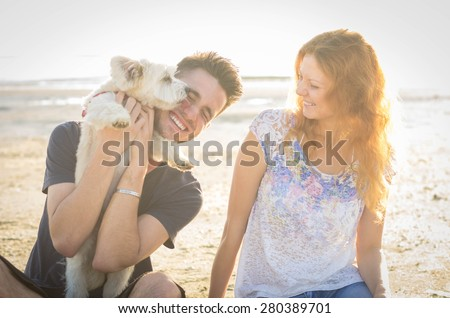 Couple of guys playing with their dog on the beach