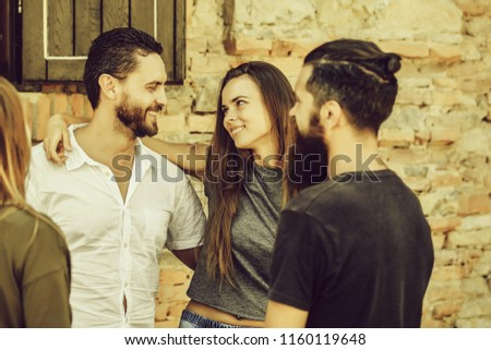 Couple of handsome bearded man with long beard and stylish hair and blonde pretty cute sexy woman or girl embracing and smiling to they friends on summer sunny day on stony wall background. #1160119648