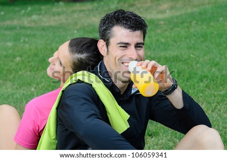 Couple of happy athletes taking a break, and smiling while the male drinks orange juice.