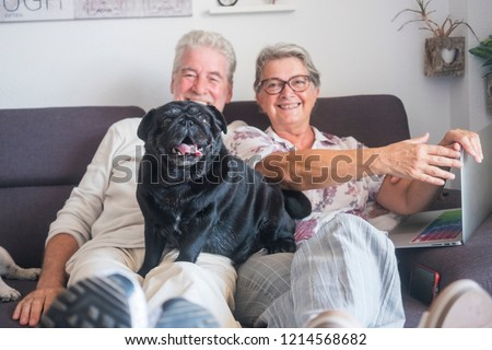 Couple of happy caucasian mature adult people man and woman sitting on the couch with a laptop and black funny pug dog over him looking at the camera with crazy expression. Couple having fun