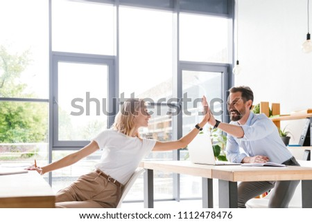 Couple of happy colleagues giving high five while sitting at the office