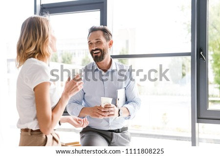 Couple of happy colleagues talking while standing at the office window with cups of coffee
