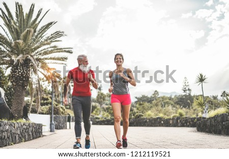 Couple of happy fitness friends running outdoor - Joggers people training at evening time after work - Jogging, healthy lifestyle and sport concept - Main focus on senior tattoo man face #1212119521