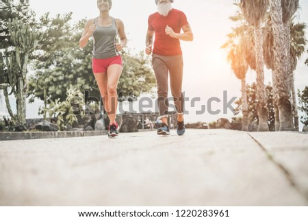 Couple of happy fitness friends running outdoor - Joggers people training at evening time after work - Jogging, healthy lifestyle and sport concept - Focus on man's shoes #1220283961