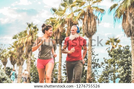 Couple of happy fitness friends running outdoor - Joggers people training in a tropical place - Jogging, healthy lifestyle and sport concept - Focus on man's face #1276755526