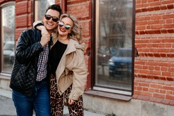 Couple of happy people hugging in the city. A man and a woman of European appearance in sunglasses on the street in outerwear.