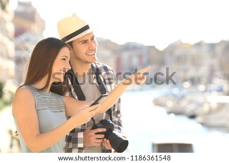Couple of happy tourists sightseeing in a coast town street #1186361548