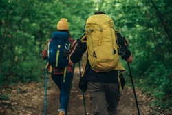 Couple of hikers enjoying the walk in nature while using trekking poles and wearing backpacks with a camping gear