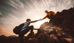 Couple of hikers helping each other climbing a mountain at sunset. People giving a helping hand and active sport concept.