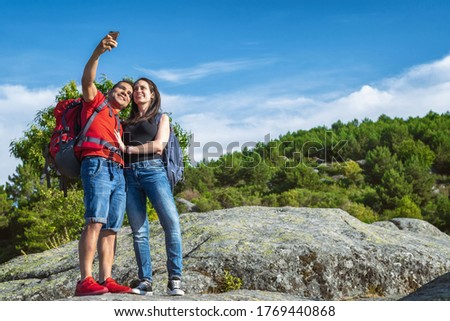 Couple of hikers in the mountains taking a photo with their mobile