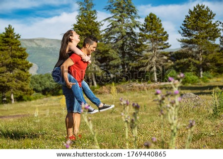 Couple of hikers in the mountains, the man catches the girl on the back and have fun