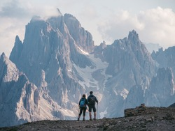 Couple of hikers standing and admiring stunning beauty of impressive jagged peaks of Cadini di misurina mountain group in Dolomites, Italy, part of Tre Cime di Levaredo national park