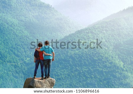 Couple of hikers standing embraced on the cliff edge and enjoying beautiful morning view in the mountains in Armenia