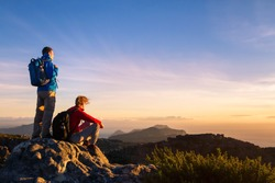 couple of hikers with backpacks enjoying panoramic view of sunset in mountains, travel and outdoor adventure concept