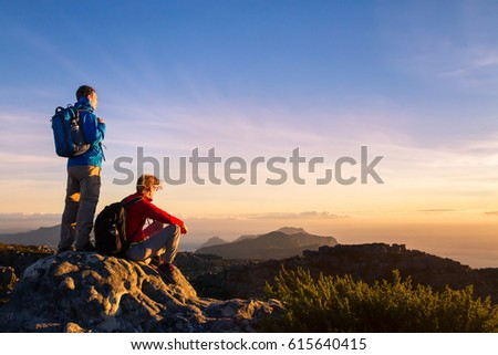 Shutterstock couple of hikers with backpacks enjoying panoramic view of sunset in mountains, travel and outdoor adventure concept