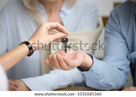 Couple of homeowners getting key to new house apartment from realtor, happy real estate owners make purchase deal, family mortgage investment and buying property concept, close up view of hands