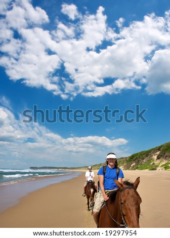 Couple of horse riders on beach under dramatic skies. Shot in Sodwana Bay Nature Reserve, KwaZulu-Natal province, Southern Mozambique area, South Africa.