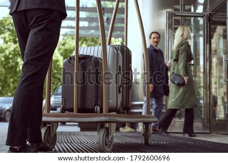 Couple of hotel guests entering a hotel while looking back at a porter managining a trolley with their suitcases Сток-фото ©