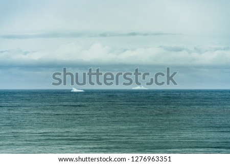 Stock Photo Couple of icebergs floating in the Atlantic ocean outside the northern Icelandic coastline. Turquoise water  all the way to the horizon and low floating white clouds, creating a sense of solitude