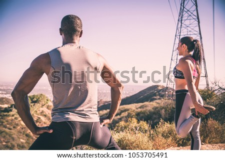 Couple of  joggers doing stretching before starting to run #1053705491