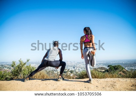 Couple of  joggers doing stretching before starting to run #1053705506