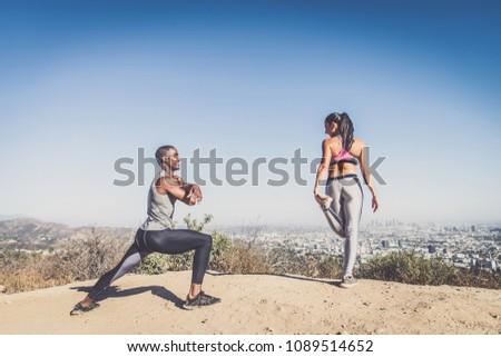 Couple of  joggers doing stretching before starting to run #1089514652
